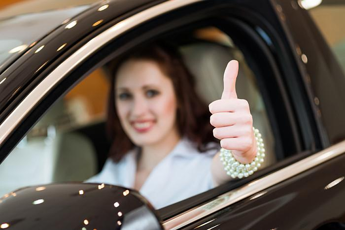 kozzi-4674956-young woman in a car and showing a thumbs up-882x589