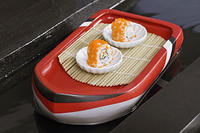 kozzi-two shushi in white plate on toy boat-1774x1183